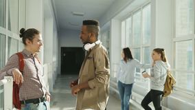 Multi-ethnic group of students talking in corridor of university having break. On front view guys are chatting to each. Multi-ethnic group of diverse students stock footage