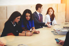 Multi ethnic group of a successful entrepreneurs talking among themselves while waiting for the beginning of the briefing Royalty Free Stock Images