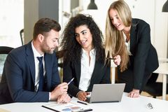 Multi-ethnic group of three businesspeople meeting in a modern o Royalty Free Stock Photography