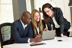 Multi-ethnic group of three businesspeople meeting in a modern o. Ffice. Two caucasian women and a black men wearing suit looking at a laptop computer stock photo
