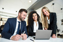 Multi-ethnic group of three businesspeople meeting in a modern o Royalty Free Stock Image