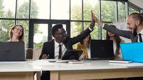 Multi ethnic group of young business people successfully finished the project and giving hand- five to each other stock video footage