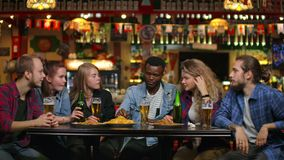 Multi-ethnic group of young men and women drinking beer at a bar and having a fun discussion about the university.  stock video footage