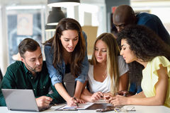 Multi-ethnic group of young men and women studying indoors. Five young people studying on white desk. Beautiful women and men working together wearing casual Royalty Free Stock Image