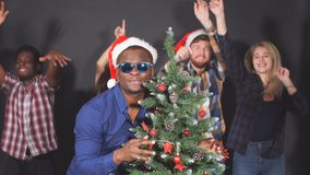 Multi ethnic group of young people at Christmas party in studio, dancing and smiling into camera. stock footage