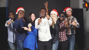 Multi ethnic group of young people at Christmas party in studio, dancing and smiling into camera. stock video footage