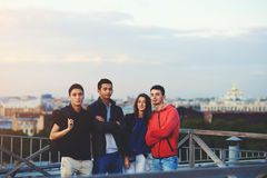 Multi ethnic group of young people posing while standing on a building roof against beautiful city landscape and evening sky. Friends dressed in stylish Royalty Free Stock Photo
