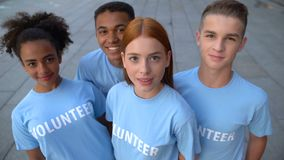 Multi-ethnic group of young volunteers looking camera, altruistic activity, help stock footage