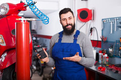 Multi-ethnic guy is calculating sum for repairing motorcycle. In workshop Stock Photography