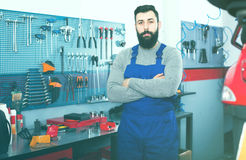 Multi-ethnic guy is showing his workplace. And tools in motorcycle workshop Royalty Free Stock Photography