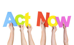 Multi-Ethnic Hands Holding The Words Act Now royalty free stock photo
