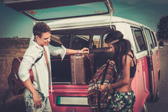 Multi-ethnic hippie couple with guitar packing luggage for a road trip.  Stock Image