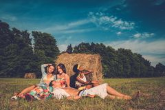 Multi-ethnic hippie friends in a field. Multi-ethnic friends relaxing near stack in a field Royalty Free Stock Image