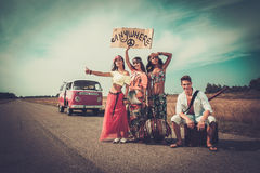 Multi-ethnic hippie hitchhikers with guitar and luggage on a road Stock Photos