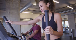 Multi-ethnic Hispanic and Black couple finishing work out at gym and getting off machines Stock Photography