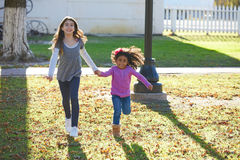 Multi ethnic kid girls playing running in park Royalty Free Stock Images