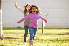 Multi ethnic kid girls playing running in park Stock Photos