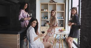 Multi ethnic ladies in amazing stylish pajamas enjoy the time together in a modern apartment design holding glasses of. Wine and looking straight to the camera stock footage