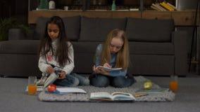 Multi ethnic little girlfriends doing homework stock video