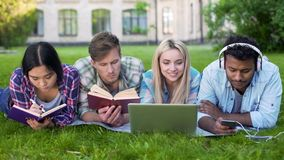 Multi-ethnic men and women doing homework on grass on campus, higher education