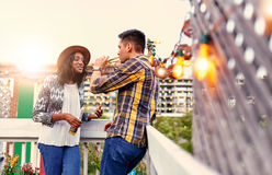 Multi-ethnic millenial couple flirting while having a drink on rooftop terrasse at sunset Royalty Free Stock Photo