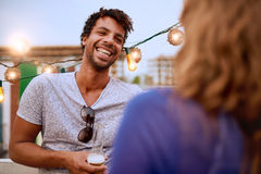 Multi-ethnic millenial couple flirting while having a drink on rooftop terrasse at sunset Royalty Free Stock Photography
