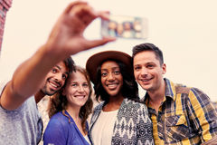 Multi-ethnic millenial group of friends taking a selfie photo with mobile phone on rooftop terrasse at sunset royalty free stock image