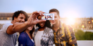 Multi-ethnic millenial group of friends taking a selfie photo with mobile phone on rooftop terrasse at sunset. Four young casual friends having fun taking Royalty Free Stock Image