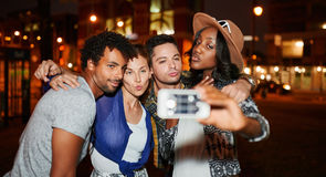 Multi-ethnic millenial group of friends taking a selfie photo with mobile phone on rooftop terrasse using flash at night Royalty Free Stock Image