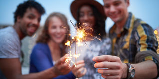 Multi-ethnic millenial group of friendsfolding sparklers on rooftop terrasse at sunset Royalty Free Stock Photos