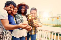 Multi-ethnic millenial group of friendsfolding sparklers on rooftop terrasse at sunset Stock Images