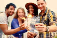 Multi-ethnic millenial group of friendsfolding sparklers on rooftop terrasse at sunset Stock Photos