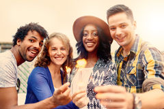Multi-ethnic millenial group of friendsfolding sparklers on rooftop terrasse at sunset Royalty Free Stock Photography