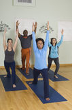 Multi Ethnic People Exercising. Full length of multi ethnic people exercising with arms raised stock photography