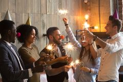 Multi-ethnic people holding sparklers and glasses celebrating Ne. Multi-ethnic people wearing funny hats holding sparklers and glasses celebrating New year Stock Image