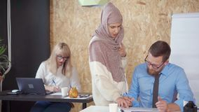 Multi ethnic people are working office of company together. Man and women of different ethnic and faiths are in office. Moslem female worker is communicating stock footage