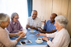 Multi-ethnic senior friends playing cards at table. Multi-ethnic senior friends playing cards while enjoying coffee at table in nursing home stock photos