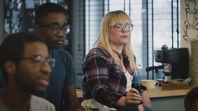 Multi-ethnic serious students at a meeting. Slow motion. Serious Caucasian girl in glasses listens carefully with drink stock video footage