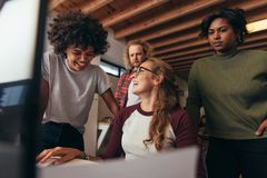 Multi-ethnic startup business team working together. In office. Woman sitting at her desk laughing with team standing by. Business team having casual talk while stock image