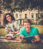 Multi ethnic students couple in a city park Royalty Free Stock Image