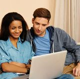 Multi ethnic students couple with laptop Stock Image