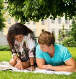 Multi ethnic students couple in a park Stock Image