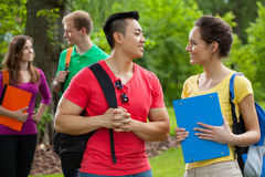 Multi-ethnic students with folders and backpacks. Outdoors Stock Images