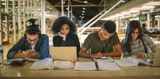 Multi-ethnic students sitting at college library stock images