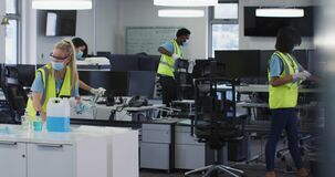 Team wearing hi vis vest and face mask cleaning the office using disinfectant