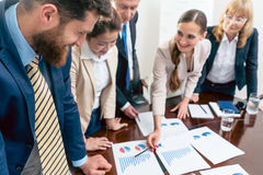 Multi-ethnic team of dedicated specialists smiling anaylizing business graphs. Multi-ethnic team of five dedicated specialists smiling while analyzing various Royalty Free Stock Photo
