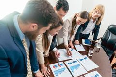 Multi-ethnic team of five dedicated specialists smiling while an. Alyzing various charts with positive statistics about the profit and the development of the Royalty Free Stock Photos