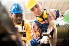 Lathe Operators Adjusting Machine. Multi-ethnic team of lathe operators wearing overalls and hardhats gathered together at production department of modern plant royalty free stock photos