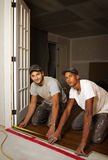 Multi ethnic team working on flooring Royalty Free Stock Image