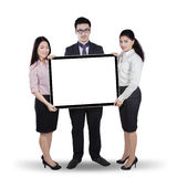 Multi ethnic teamwork holding whiteboard Royalty Free Stock Photo